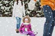 Happy family with sled walking in winter forest Stock Photos