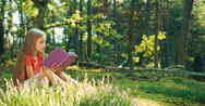 Hiker girl 8-9 years child reading book sitting on the grass and laughing Stock Footage