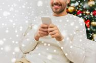 Smiling man with smartphone at home for christmas Stock Photos