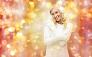 Smiling young woman in winter earmuffs and sweater Stock Photos