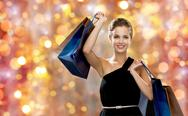 Smiling woman in dress with shopping bags Stock Photos