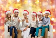 Happy family in santa hats showing thumbs up Stock Photos