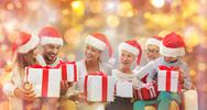 Happy family in santa hats with gift boxes Stock Photos