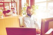 Happy creative male office worker with computer Stock Photos