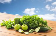 Close up of bottle with green juice and vegetables Stock Photos