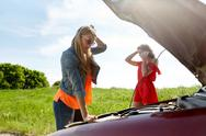 Women with open hood of broken car at countryside Stock Photos