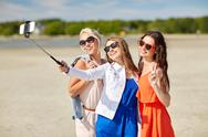 Group of smiling women taking selfie on beach Stock Photos