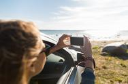Happy young woman in car with smartphone at sea Stock Photos