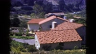 1953: spanish architecture style clay roof tile houses overlooking ocean cliff Stock Footage