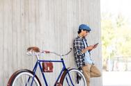Man with smartphone, earphones and bicycle Stock Photos