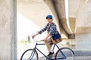 Happy hipster man with bag riding fixed gear bike Stock Photos