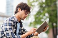 Man with tablet pc sitting on city street bench Stock Photos