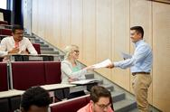 Teacher giving tests to students at lecture Stock Photos