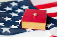 Close up of american flag, wedding rings and bible Stock Photos