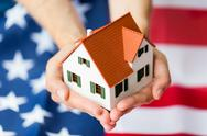 Close up of hands holding house over american flag Stock Photos
