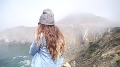 A young woman sitting on top of a cliff with the Bixby Creek Bridge in the backg Stock Footage