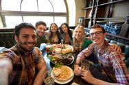 Happy friends taking selfie at bar or pub Stock Photos