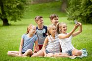 Happy kids or friends taking selfie in summer park Stock Photos