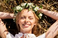 Happy woman in wreath of flowers lying on straw Stock Photos
