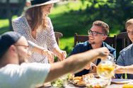 Happy friends having dinner at summer garden party Stock Photos