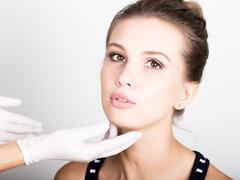 Beautician hand's examining beautiful young female face Stock Photos
