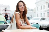 Happy woman sitting in outdoor cafe Stock Photos