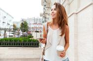 Girl walking on the street and drinking take away coffee Stock Photos