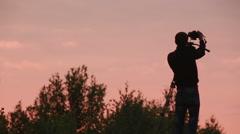 Cameraman shooting sunset sky Stock Footage