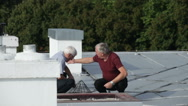 Seniors checking and maintaining rooftop Stock Footage