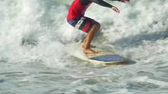 A male surfer riding a wave and a second surfer jumps on on a longboard surfboar Stock Footage