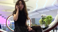 Beautiful young woman in black talking on her phone in a modern interior. 4K Stock Footage