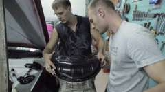 Two mechanics try on the size of the items to be installed Stock Footage
