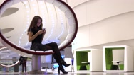 Brunette girl in black using her phone in a modern interior. 4K video Stock Footage