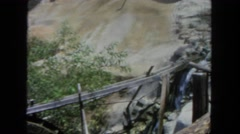 1962: water flows through gold mining area with tourists  Stock Footage