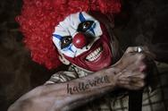 Evil clown with the word Halloween in his arm Stock Photos