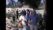 1962: woman is putting letters in her handbag as she and her husband stand in Stock Footage