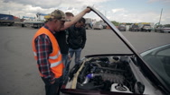 A group of people check the condition of the car engine Stock Footage