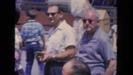 1962: two older men in crowd of people in park take their sunglasses off  Stock Footage