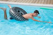 Boy is enjoying swimming pool on summer Stock Photos