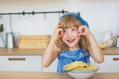 Portrait of a little girl funny eats a spaghetti from a dish and puts out a t Stock Photos