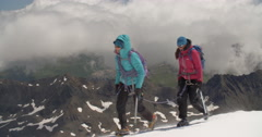 Mountaineers Traverse Glacier on High Altitude Mountain Above Clouds. Stock Footage