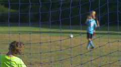 A soccer game through a soccer football goal net. Stock Footage