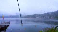 Alone at lake on the rainy day. Clear umbrella and raindrops dripping Stock Footage