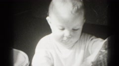 1947: baby chewing on newspaper MIDDLETOWN Stock Footage
