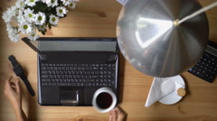 A woman working at a computer with smart watches, coffee and bouquet of flowers. Stock Footage