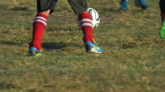 Details of a ball and boys legs playing youth soccer football on a green field. Stock Footage