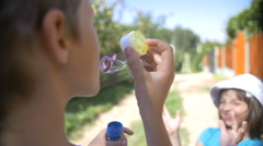 Boy blowing bubbles, a girl trying to catch soap bubbles, slow motion Stock Footage