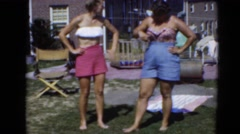 1947: women standing in summer with bathing suits and shorts on in yard Stock Footage