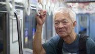 Asian Senior travel backpack in Japanese train for holiday Stock Footage