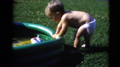 1947: baby crawling into kiddie pool in the backyard with his brother  Stock Footage